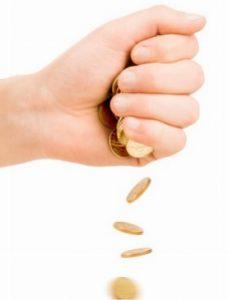 Eine geschlossene Hand, aus der mehrere Münzen fallen.